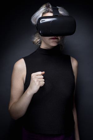gamers: Woman wearing a futuristic looking virtual reality headset goggles.  The device is technology that lets video gamers experience VR or AR augmented reality
