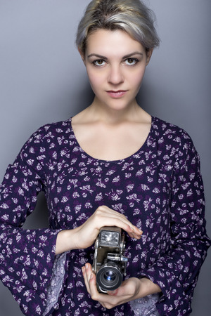 filmmaker: Film student posing with a classic video camera advertising for movie industry or art schools.  She can depict a director, cinematographer, filmmaker or a camerawoman.