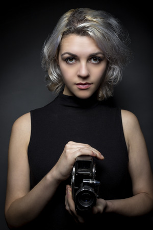 filmmaker: Female actor posing with a vintage camera as an artistic director, creative cinematographer or filmmaker.  She is advertising the movie industry or film art schools.