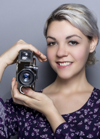 Film student posing with a classic video camera advertising for movie industry or art schools.  She can depict a director, cinematographer, filmmaker or a camerawoman.
