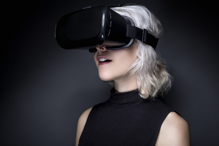 invent: Woman wearing a futuristic looking virtual reality headset goggles.  The device is technology that lets video gamers experience VR or AR augmented reality