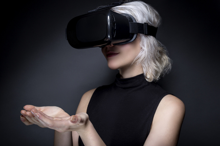 Woman wearing a virtual reality headset touching or holding something.  She is interacting with something she is watching or playing a video game.  The image depicts VR and AR technology. Stock Photo - 70023045