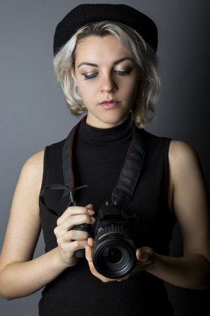 self employed: Female professional or amateur photographer holding a dslr camera.  This photographic gear is used by both self employed artists and journalists or for tourism and hobbies.
