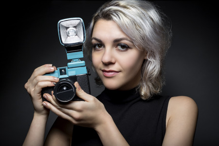 Female photographer holding a classic, vintage plastic film camera.  The woman is depicting the basic fundamentals of photography with antique gear. This creative hobby is popular among hipsters.