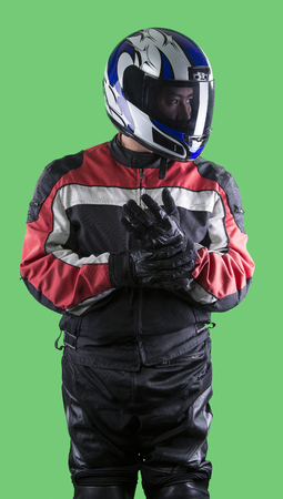 Male wearing protective leather and textile suit for racing race cars or motorcycles.  The armor is worn in professional motor sports.  The man is on a green screen or chroma key background. Stock Photo