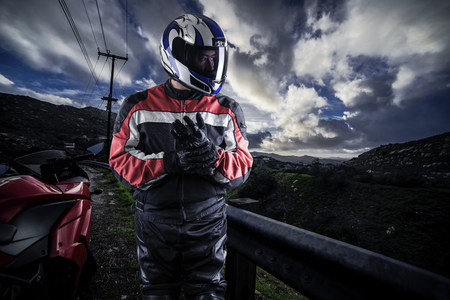 Male motorcyclist wearing protective leather racing suit with a red bike or motorcycle on an open road.  The image is shot in HDR and composite.  The vehicle is cropped to become generic non branded. The image depicts travel and adventure. Stock Photo
