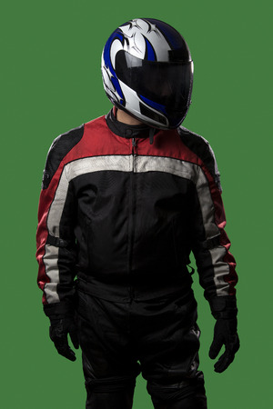 Male wearing protective leather and textile suit for racing race cars or motorcycles.  The armor is worn in professional motor sports.  The man is on a green screen or chroma key background. Archivio Fotografico