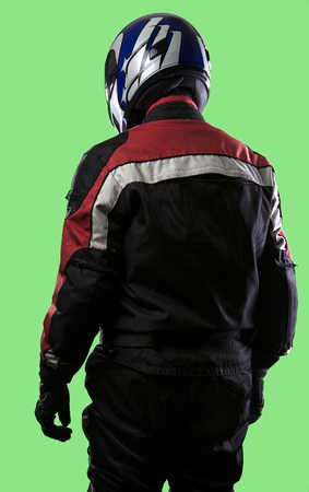 gran prix: Male wearing protective leather and textile suit for racing race cars or motorcycles.  The armor is worn in professional motor sports.  The man is on a green screen or chroma key background. Stock Photo