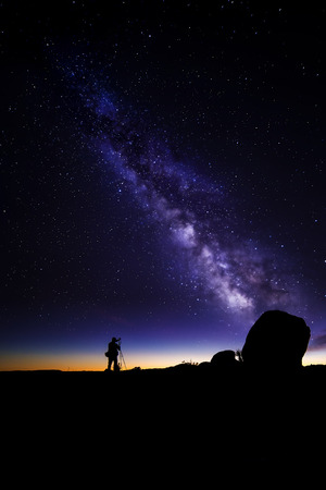stary: Photographer doing astro photography in a desert nightscape with milky way galaxy.  The background is stary celestial bodies in astronomy.  The heaven depicts science and the divine.