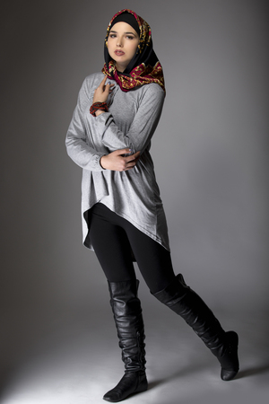 Multiracial female wearing a stylish red hijab mostly associated with middle east, islamic, and eastern european cultures.  The image depicts conservative modern fashion.