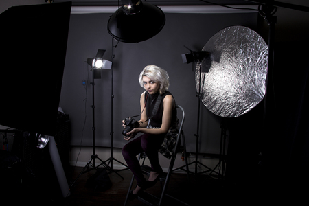 Creative female professional photographer in a strobe lighting studio.  She portrays an independent self employed freelance entrepreneur.  The image depicts the photography arts.