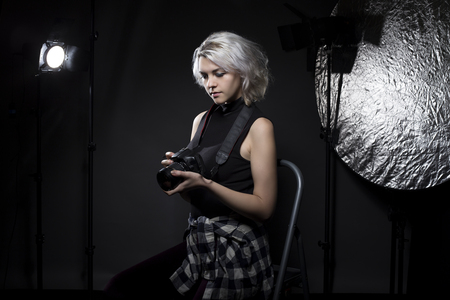 self employed: Creative female professional photographer in a strobe lighting studio.  She portrays an independent self employed freelance entrepreneur.  The image depicts the photography arts.