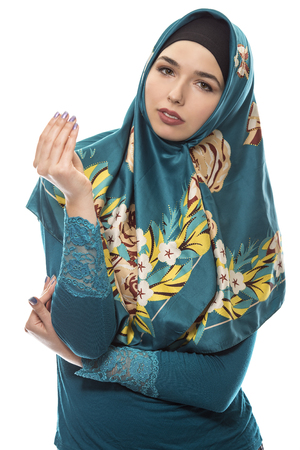 conservative: Female wearing a hijab, conservative fashion for muslims, middle east and eastern european culture.  She is isolated on a white background and showing money gesture