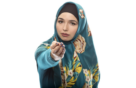Female wearing a hijab, conservative fashion for muslims, middle east and eastern european culture.  She is isolated on a white background and pointing forward