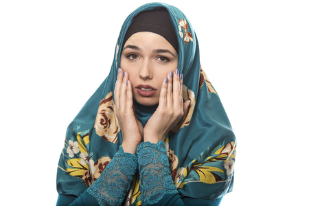 conservative: Female wearing a hijab, conservative fashion for muslims, middle east and eastern european culture.  She is isolated on a white background and looking scared Stock Photo