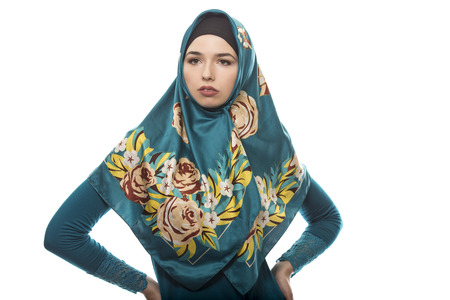 Female wearing a hijab, conservative fashion for muslims, middle east and eastern european culture.  She is isolated on a white background and looking confident and strong Stock Photo