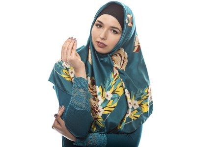 wage earner: Female wearing a hijab, conservative fashion for muslims, middle east and eastern european culture.  She is isolated on a white background and showing money gesture