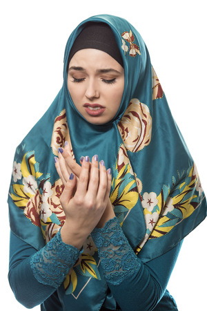 intolerable: Female wearing a hijab, conservative fashion for muslims, middle east and eastern european culture.  She is isolated on a white background and looking disgusted by something Stock Photo