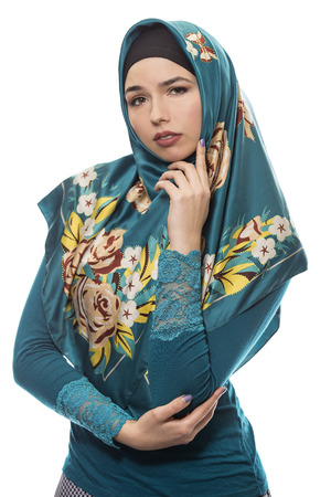 Female wearing a hijab, conservative fashion for muslims, middle east and eastern european culture.  She is isolated on a white background and looking worried of failure