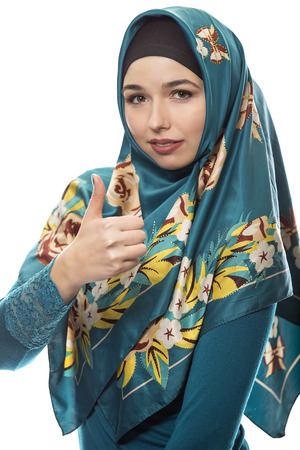 Female wearing a hijab, conservative fashion for muslims, middle east and eastern european culture.  She is isolated on a white background with thumbs up for approval