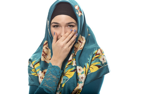 Female wearing a hijab, conservative fashion for muslims, middle east and eastern european culture.  She is isolated on a white background and looking shy