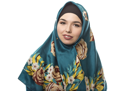Female wearing a hijab, conservative fashion for muslims, middle east and eastern european culture. She is isolated on a white background and looking happy and joyful
