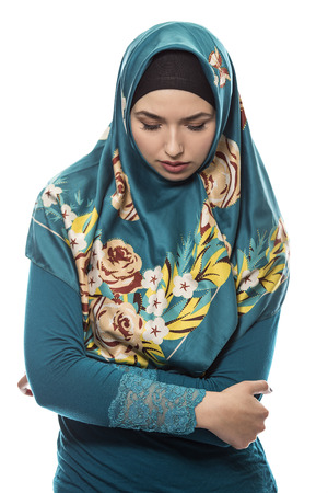 Female wearing a hijab, conservative fashion for muslims, middle east and eastern european culture.  She is isolated on a white background and looking down because she is upset at failure