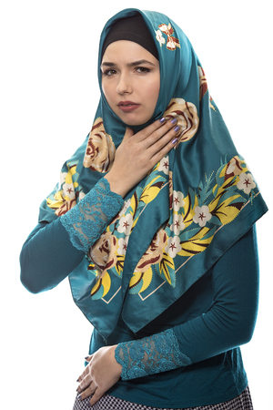 Female wearing a hijab, conservative fashion for muslims, middle east and eastern european culture.  She is isolated on a white background and grabbing her throat like she is sick