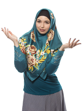 conservative: Female wearing a hijab, conservative fashion for muslims, middle east and eastern european culture.  She is isolated on a white background and looking carefree or confused