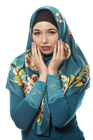 bashful: Female wearing a hijab, conservative fashion for muslims, middle east and eastern european culture.  She is isolated on a white background and looking shy