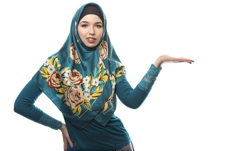 conservative: Female wearing a hijab, conservative fashion for muslims, middle east and eastern european culture.  She is isolated on a white background and advertising something.