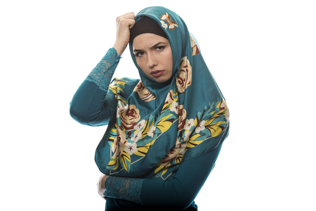 insult: Female wearing a hijab, conservative fashion for muslims, middle east and eastern european culture.  She is isolated on a white background and looking angry and upset.
