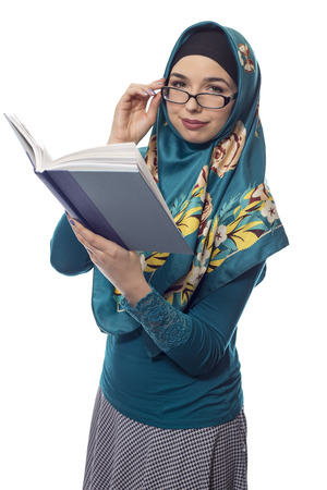 Female foreign exchange student wearing glasses and a hijab reading a text book.  The conservative outfit is associated with muslims or middle eastern and east european culture. Stock Photo