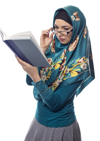 conservative: Female foreign exchange student wearing glasses and a hijab reading a text book.  The conservative outfit is associated with muslims or middle eastern and east european culture. Stock Photo