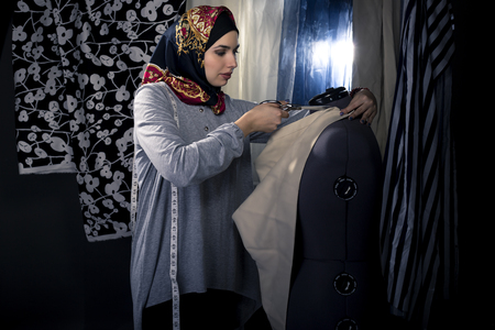 conservative: Female fashion designer tailoring conservative clothing in a textile workshop.  The hijab she is wearing is associated with muslims, middle east or eastern european cultures.  The image depicts creativity and professional seamstress craft.
