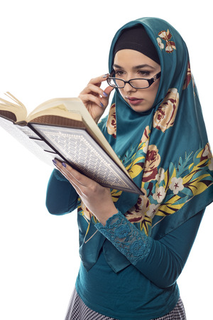 Female foreign exchange student wearing glasses and a hijab reading a text book.  The conservative outfit is associated with muslims or middle eastern and east european culture. Zdjęcie Seryjne