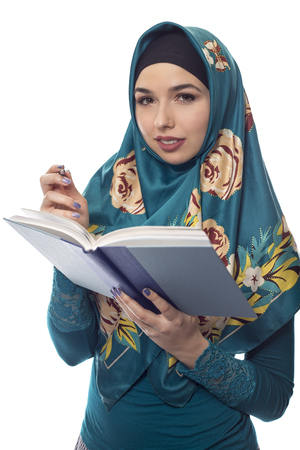 conservative: Female student author or journalist writing notes on a book with a pen.  She is wearing a hijab associated with muslims or middle eastern and east european culture.  The image depicts learning and education. Stock Photo