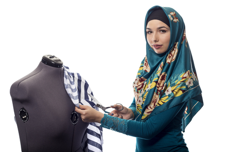 conservative: Self employed female tailor or fashion designer wearing a hijab.  Her outfit is associated with muslim and middle eastern or east european culture.  She is isolated on a white background. Stock Photo
