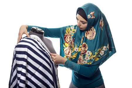 Self employed female tailor or fashion designer wearing a hijab.  Her outfit is associated with muslim and middle eastern or east european culture.  She is isolated on a white background. Stock Photo