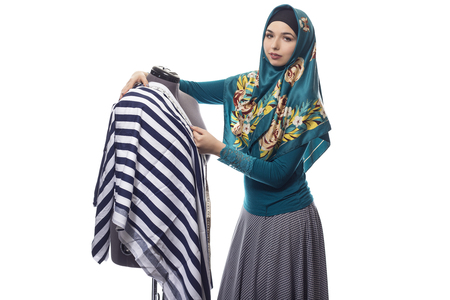 Self employed female tailor or fashion designer wearing a hijab.  Her outfit is associated with muslim and middle eastern or east european culture.  She is isolated on a white background. Zdjęcie Seryjne