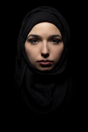 conservative: Proud and confident female wearing a black hijab as a conservative fashion choice to represent feminist freedom of expression and political statement.  The headscarf is associated with muslims and middle eastern and east eauropean culture.