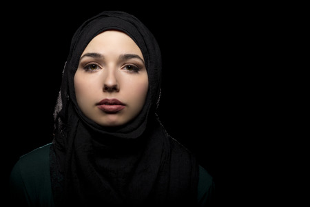 Proud and confident female wearing a black hijab as a conservative fashion choice to represent feminist freedom of expression and political statement.  The headscarf is associated with muslims and middle eastern and east eauropean culture.
