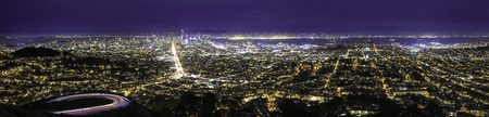 gentrification: City view at night of San Francisco.  The aerial skyline shows both the financial district or downtown metropolis as well as urban residential housing in Oakland and SF. The image depicts tourism in America. Stock Photo