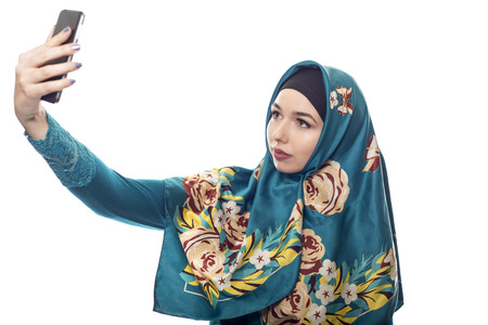 Middle Eastern or East European female proudly showing her conservative fashion via social networking by taking a selfie with a cell phone camera.  The headscarf is associated with muslim culture. Zdjęcie Seryjne