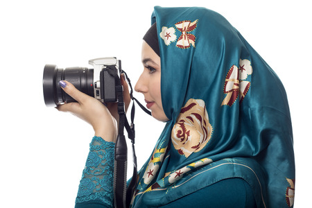 hobbyist: Female photographer wearing a hijab.  She is either a hobbyist or a journalist.  The headscarf is associated with muslims and east european or middle eastern culture.  she is holding a camera.