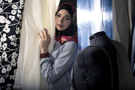 Female fashion designer tailoring conservative clothing in a textile workshop. The hijab she is wearing is associated with muslims, middle east or eastern european cultures. The image depicts creativity and professional seamstress craft.