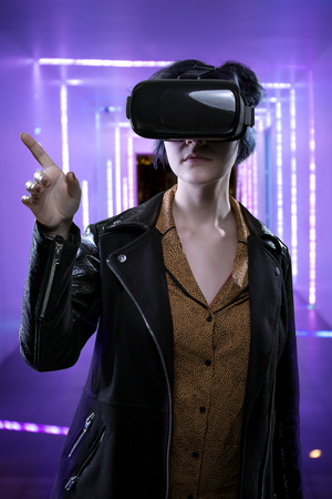 virtual reality simulator: Woman in futuristic enviroment wearing a virtual reality headset.  The image depicts modern technology and immersive leisure experiences.