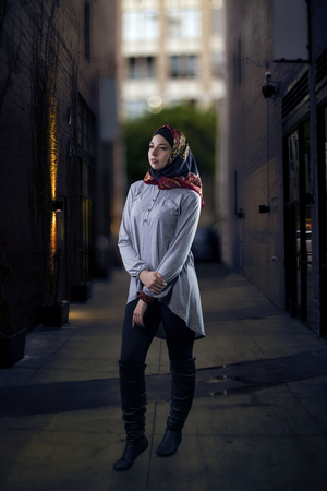 represents: Woman wearing conservative Hijab fashion while walking in a modern urban city.  The image depicts muslims who are proud to wear traditional clothing.  The female wearing religious outfit represents individualism, feminism and ethnic and racial acceptance.