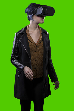 virtual reality simulator: Woman isolated on a green background or greenscreen wearing a VR virtual reality headset.  The image depicts technology and can be used for composites.