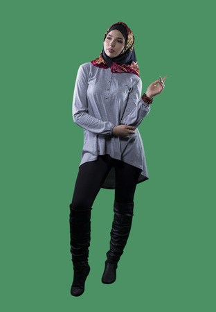 conservative: Woman wearing conservative traditional hijab with modern style clothing.  The head scarf is associated with islamic religious traditions and middle eastern or east european cultures.